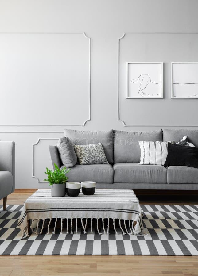 Tazas de café y planta verde en pote en la mesa de centro baja cubierta con el mantel rayado en la sala de estar moderna diseñada imagen de archivo