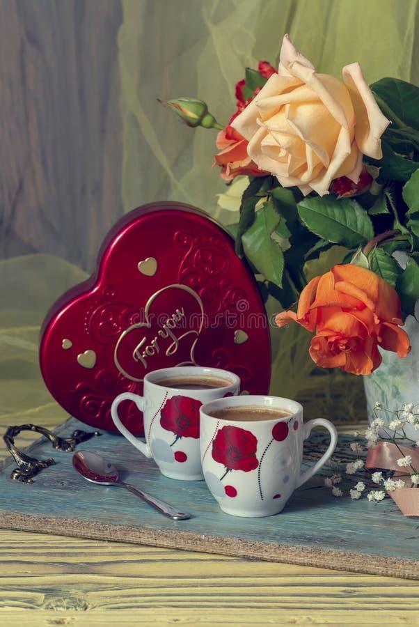 Tazas de café y un ramo de rosas imagen de archivo