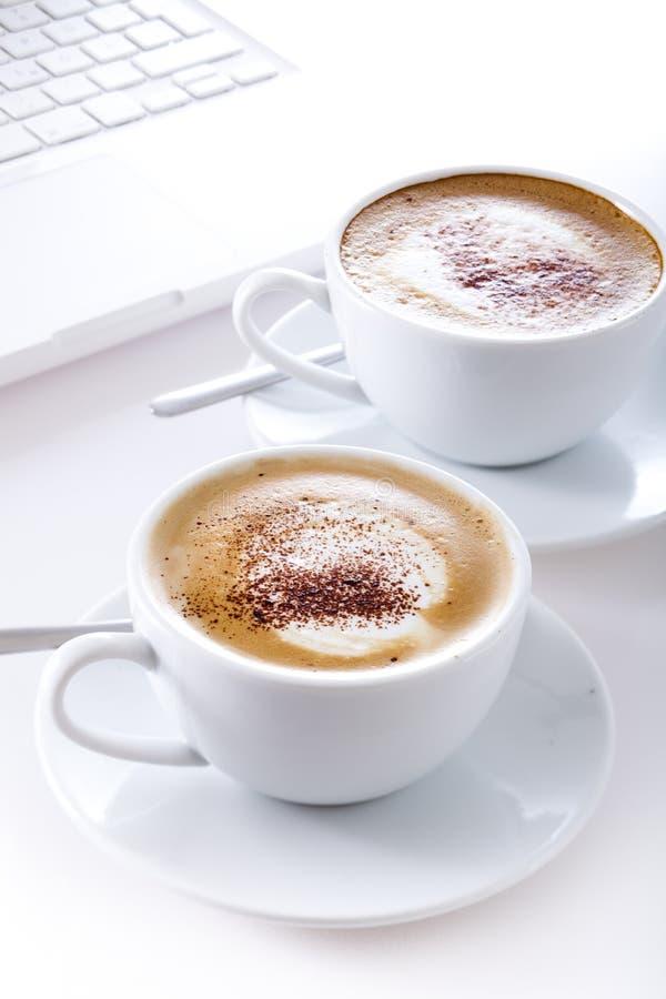 Tazas de cappuccino con la computadora portátil fotografía de archivo libre de regalías
