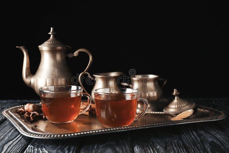 Tazas de cristal con té caliente en la bandeja contra fondo oscuro fotografía de archivo