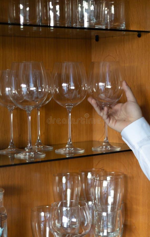 Tazas de cristal en una estantería de cristal con una mano que aparece fotografía de archivo libre de regalías