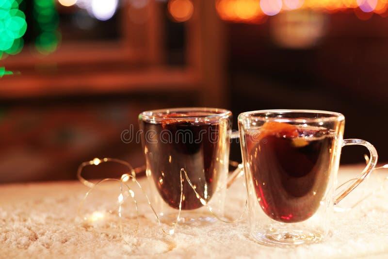 Tazas de cristal de vino reflexionado sobre y de guirnalda en la tabla cubierta con nieve al aire libre fotos de archivo