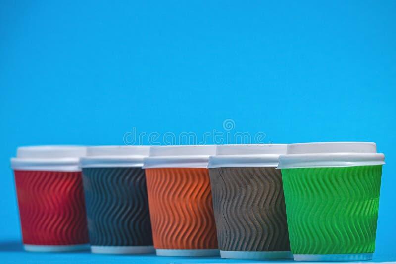 Tazas de la cartulina para no reutilizable en un fondo azul fotos de archivo libres de regalías