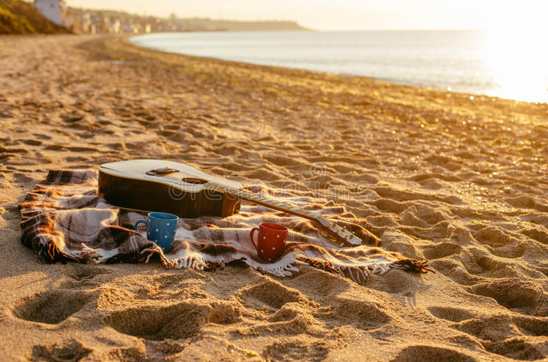 Tazas de la guitarra y de café en la playa imagenes de archivo