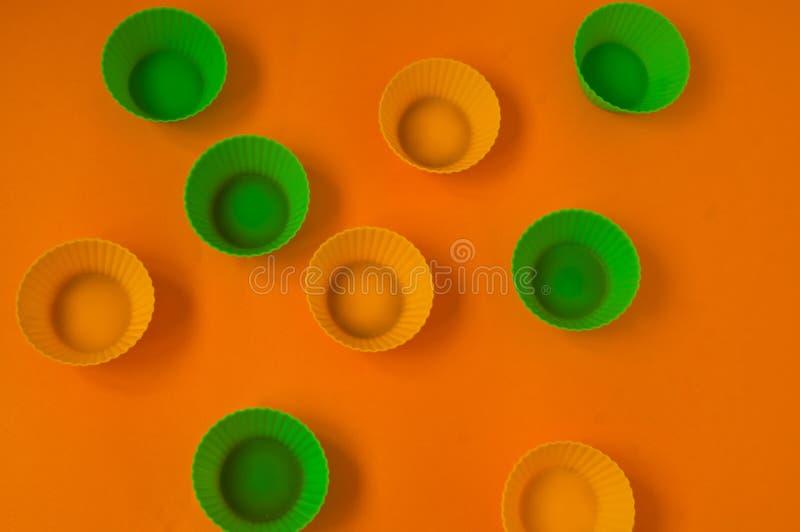 Tazas de la hornada del silicón para las magdalenas, amarillo y verde fotografía de archivo