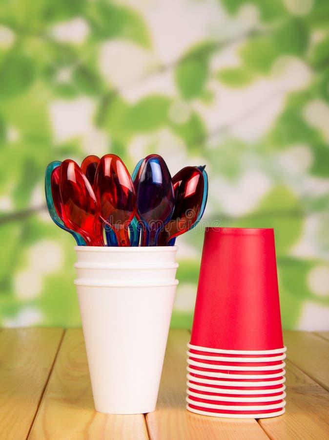 Tazas de papel disponibles y cucharas plásticas en verde abstracto brillante foto de archivo libre de regalías