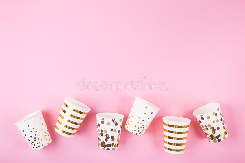 Tazas de papel en fondo rosado imagenes de archivo