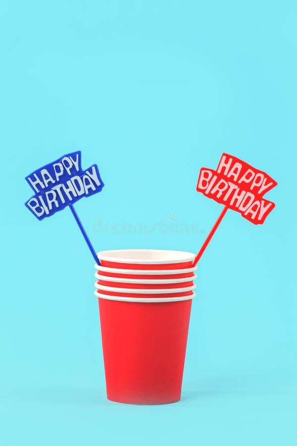 Tazas de papel rojas y puntos del feliz cumpleaños imagenes de archivo