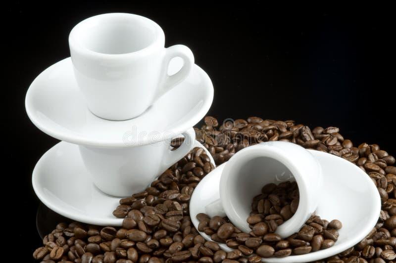 Tazas del café express en los granos de café imágenes de archivo libres de regalías
