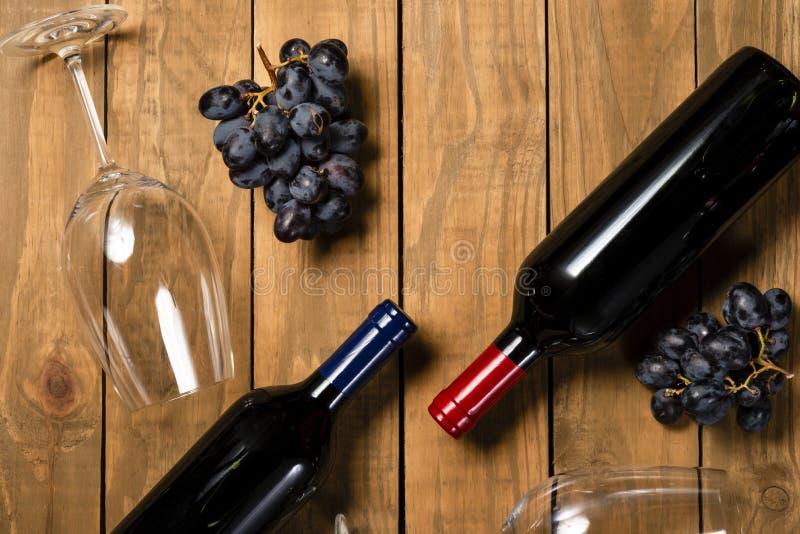Tazas del cristal de botellas de vino y manojos de la uva en fondo de madera Visión superior con el espacio de la copia foto de archivo