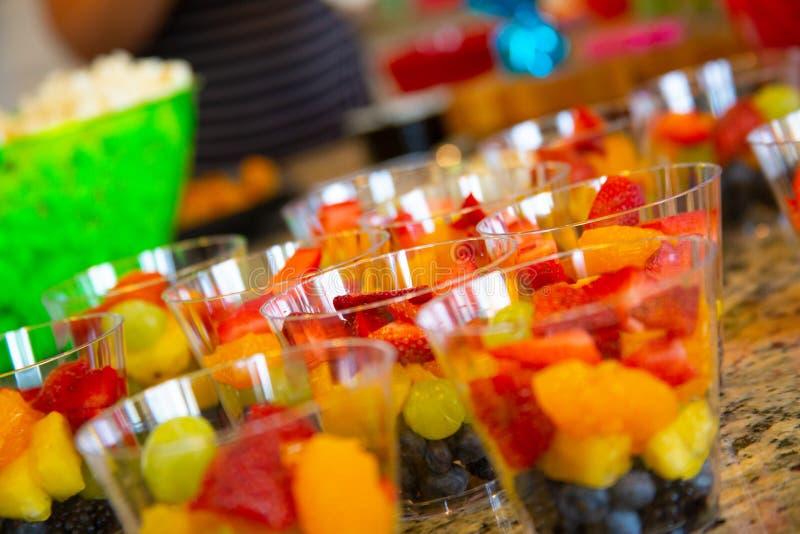 Tazas plásticas de la fiesta de cumpleaños con la fruta imagen de archivo libre de regalías