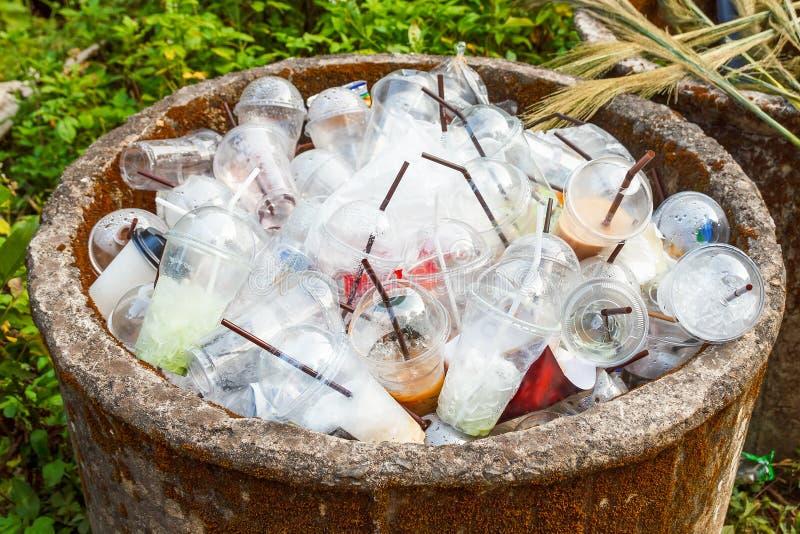 Tazas plásticas en trashcan imagenes de archivo