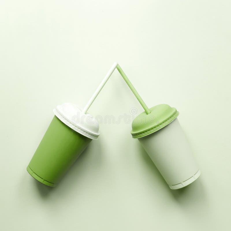 Tazas plásticas verdes greenery imagen de archivo libre de regalías