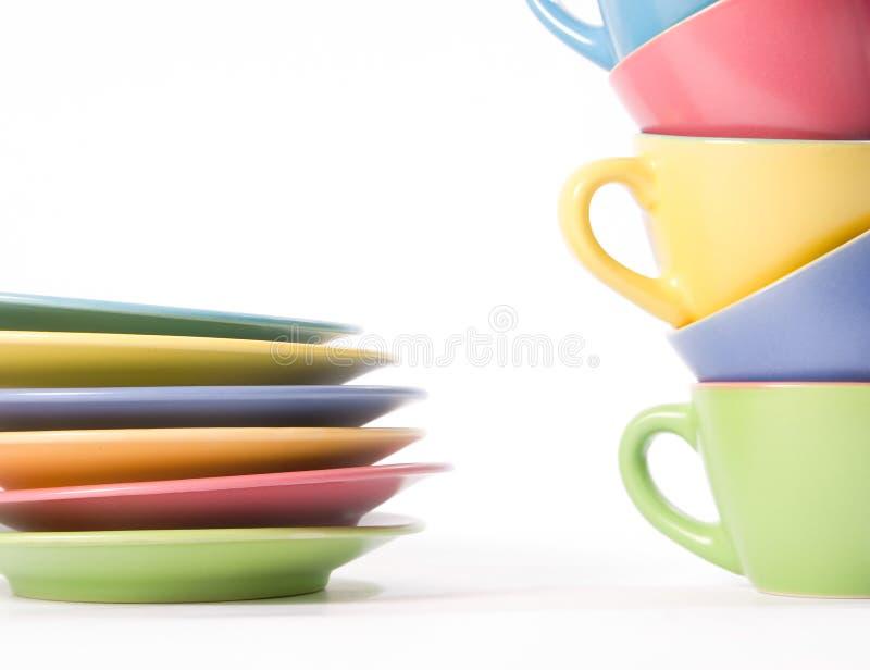 Tazas y platos coloreados de café fotografía de archivo