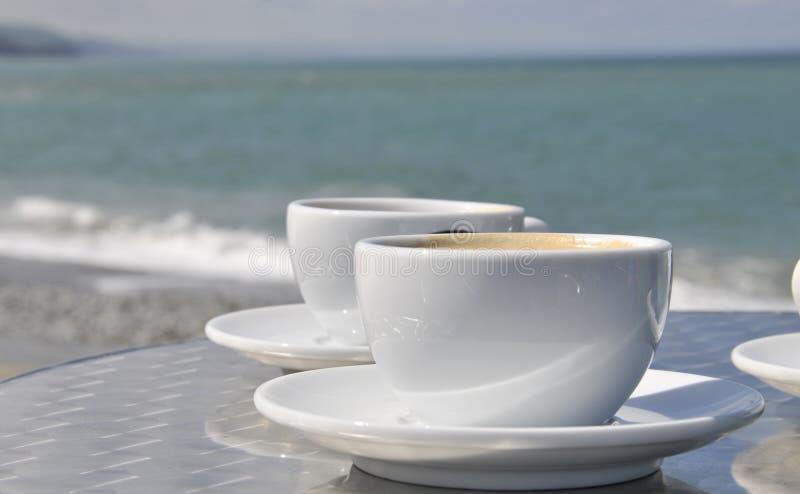 Tazas y playa de café fotos de archivo