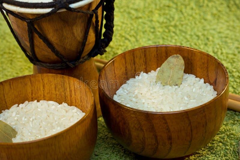 Tazones de fuente de madera con arroz y tamtam en verde imágenes de archivo libres de regalías