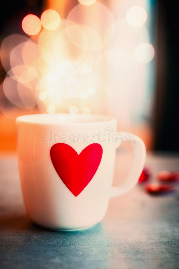 Tazza accogliente con cuore rosso sulla tavola al fondo di illuminazione del bokeh, vista frontale Simbolo di amore o giorno di b immagine stock