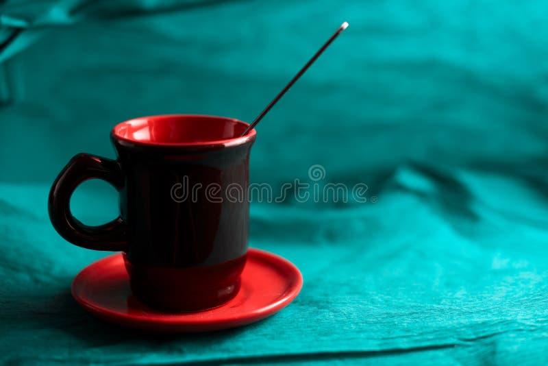 Tazza arancio rossa dell'argilla con il piattino ed il cucchiaio su fondo di carta azzurrato fotografia stock libera da diritti