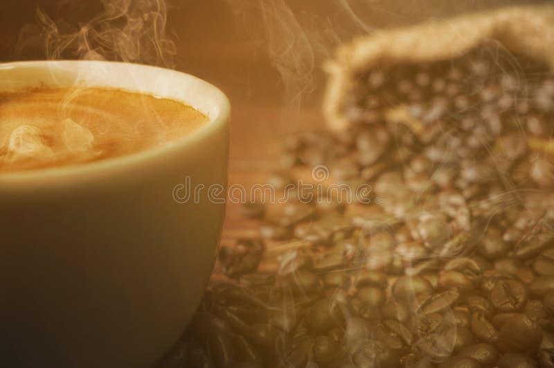 Tazza bianca calda di caffè fresco, cappuccino con fumo fragrante dorato immagine stock
