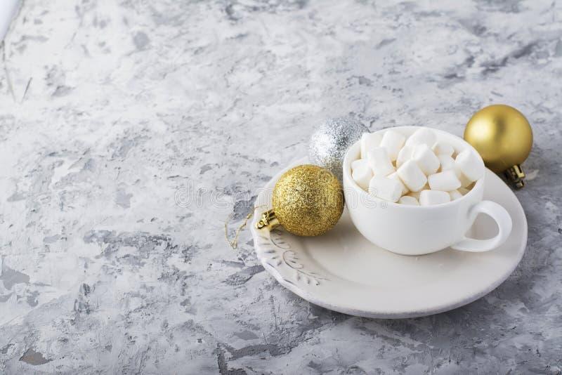 Tazza bianca ceramica piena di piccola caramella gommosa e molle per produrre la cioccolata calda di praznichnogo di inverno sul  fotografia stock