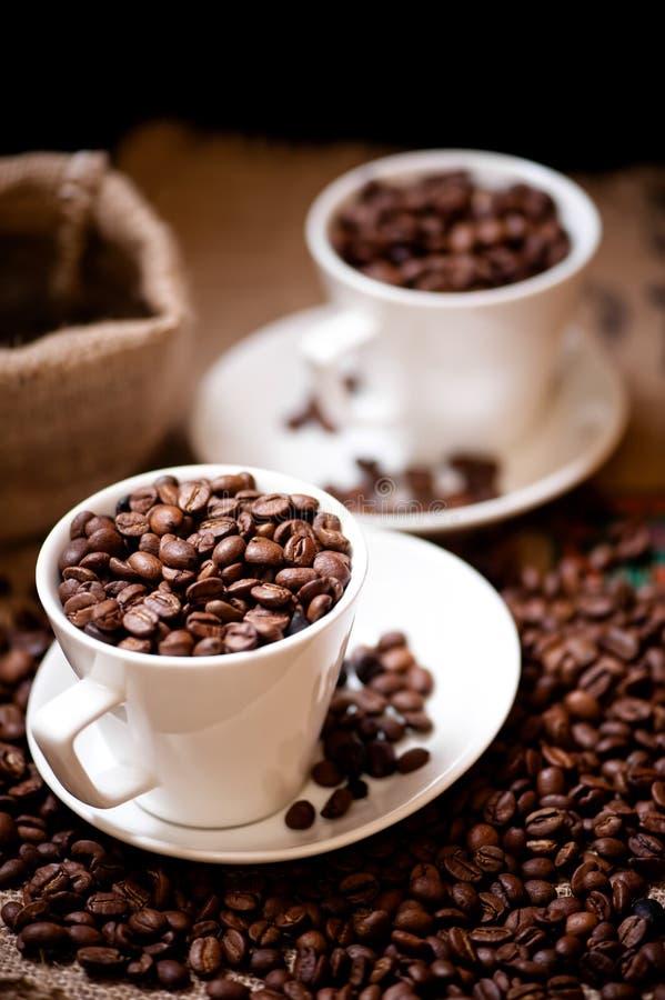Tazza bianca con bio- caffè aromatico africano e l'imballaggio d'annata fotografie stock libere da diritti