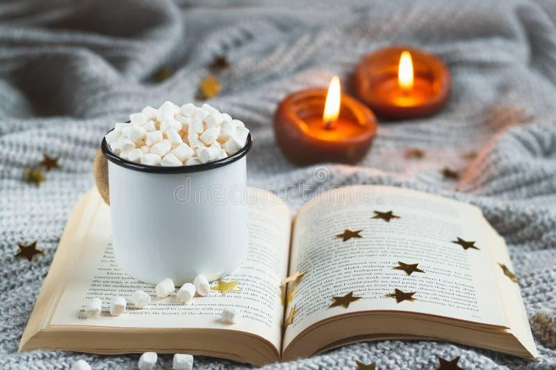 Tazza bianca con cacao e la caramella gommosa e molle su un libro aperto su un BAC strutturato grigio chiaro fotografia stock