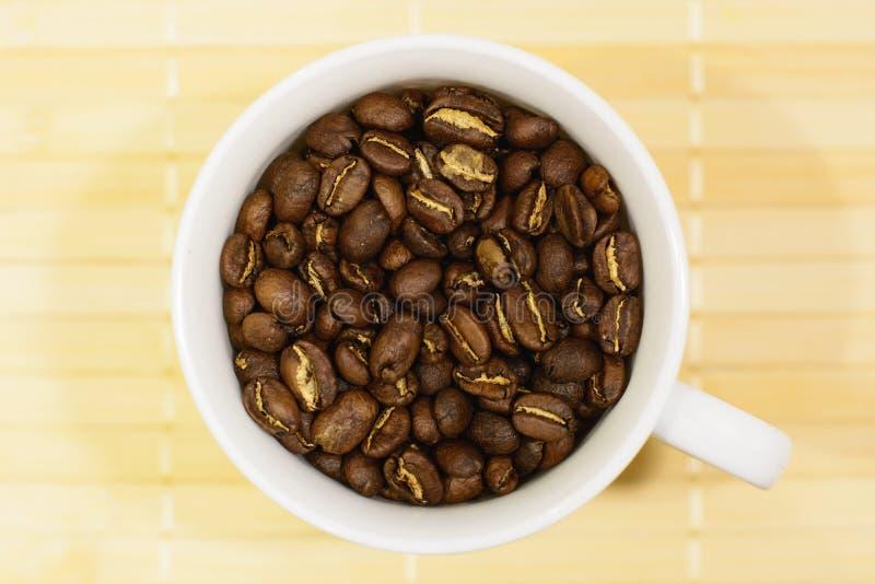 Tazza bianca con i chicchi di caffè arrostiti fotografia stock libera da diritti