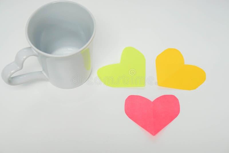 Tazza bianca con le carte variopinte del cuore immagini stock