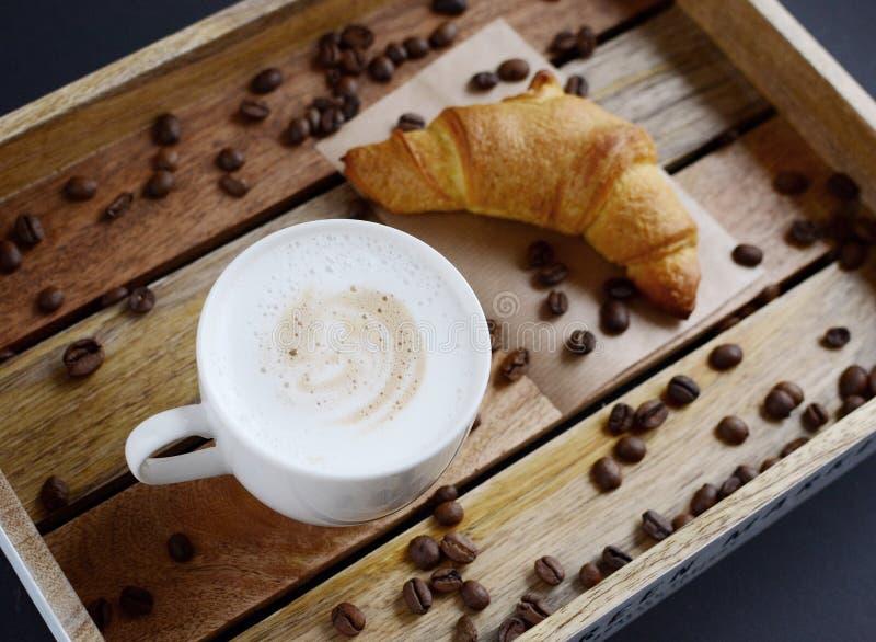 Tazza bianca di cappuccino e del croissant sul vassoio di legno fotografia stock libera da diritti