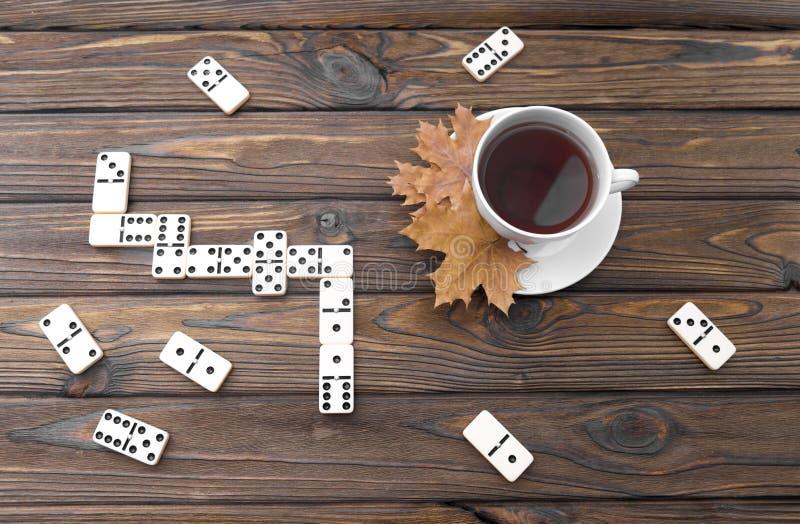 Tazza bianca di tè, foglie di acero, gioco di domino immagini stock libere da diritti