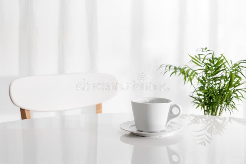 Tazza bianca sul tavolo da cucina fotografie stock libere da diritti