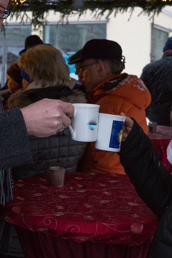 tazza calda della perforazione del vino ad un arrivo del mercato di natale a dicembre immagini stock