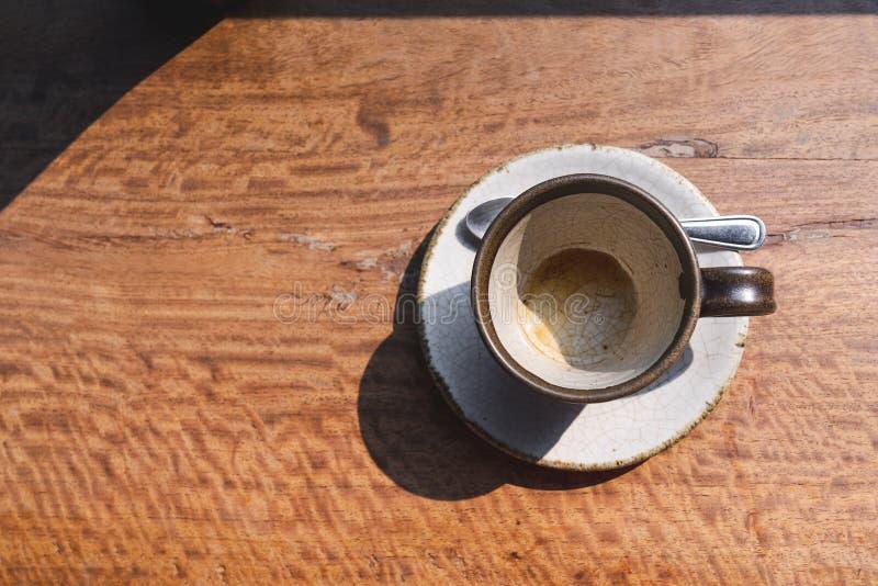 tazza ceramica del caffè vuoto di vista superiore sullo scrittorio di legno con la luce di mattina fotografia stock