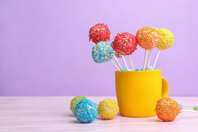 Tazza con gli schiocchi saporiti del dolce sulla tavola contro fondo lilla fotografie stock
