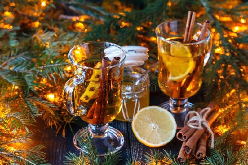 Tazza con i biscotti rossi del vin brulé o della sangria e del pan di zenzero per la festa di natale Bevanda magica sul deco del  fotografia stock