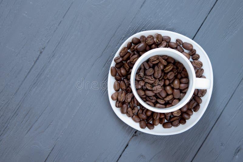 Tazza con i chicchi di caffè dentro su fondo di legno grigio fotografia stock libera da diritti