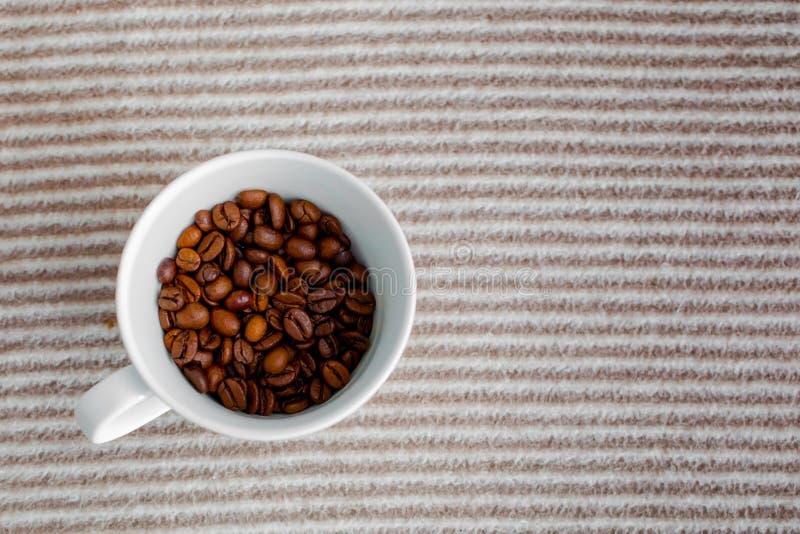 Tazza con i chicchi di caffè su fondo a strisce grigio fotografia stock libera da diritti