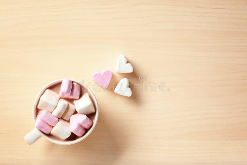 Tazza con la bevanda calda del cacao e caramelle gommosa e molle sulla tavola, vista superiore fotografia stock libera da diritti