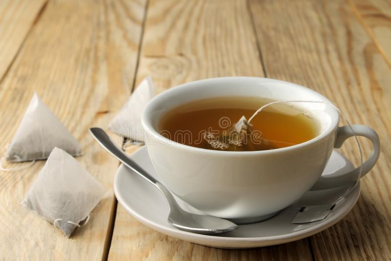 Tazza con la piramide della bustina di tè e del tè Primo piano Su una tabella di legno per produrre tè immagine stock libera da diritti