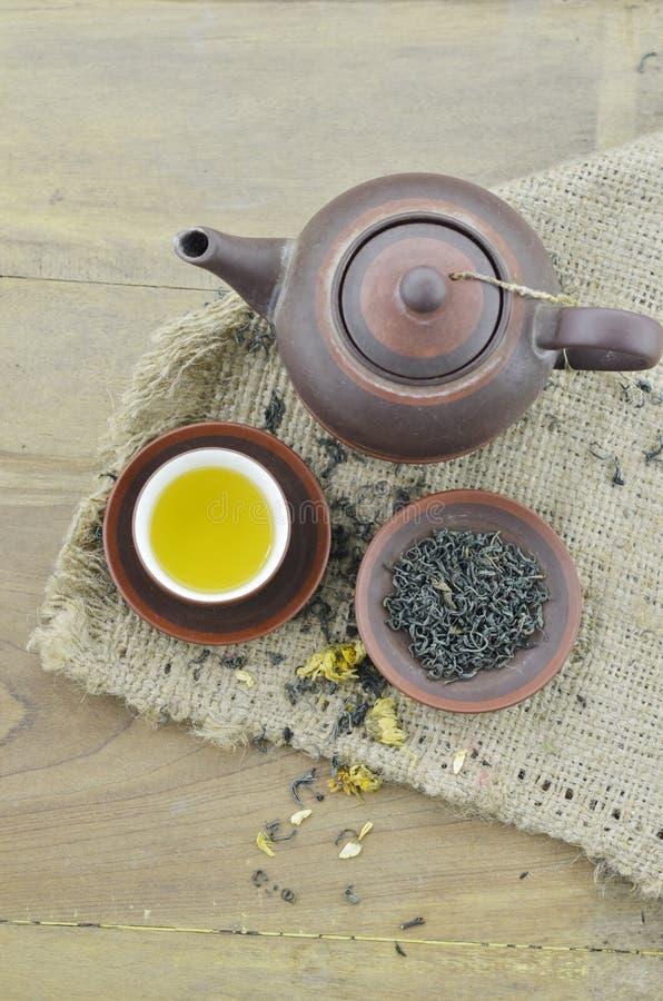 Tazza con tè e teiera sulla tavola di legno immagine stock libera da diritti