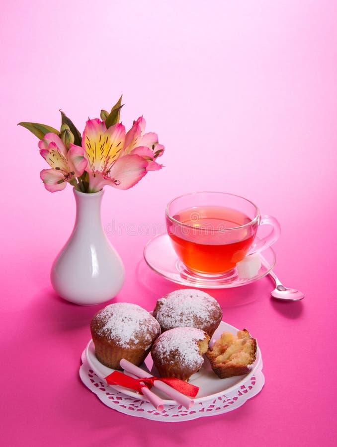 Tazza con tè, il cucchiaio ed i bigné sul piatto fotografie stock libere da diritti