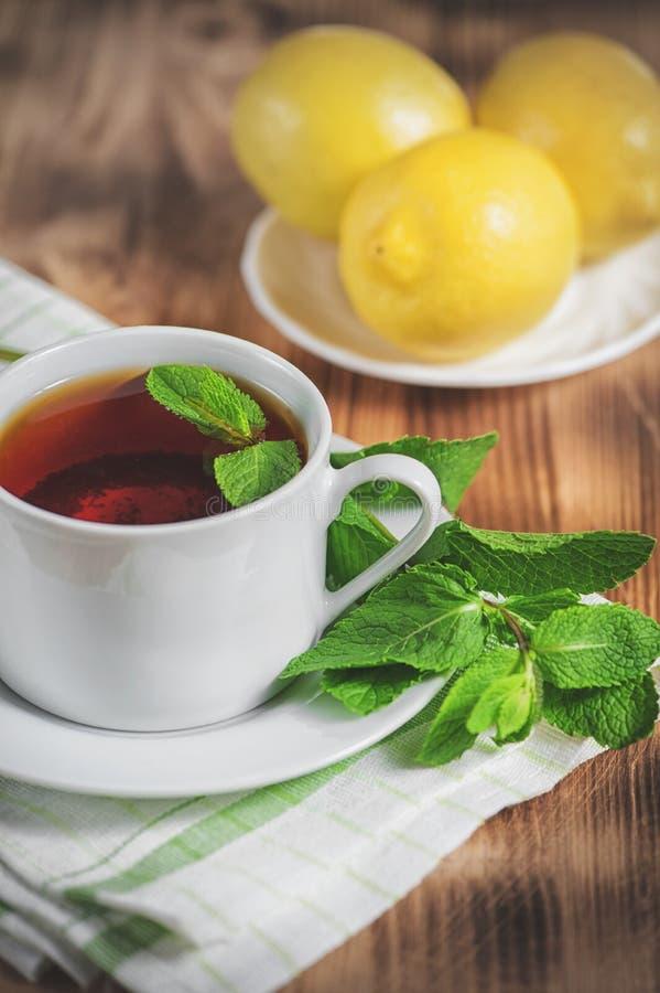 Tazza con tè, la menta ed il limone sulla vecchia tavola fotografie stock libere da diritti
