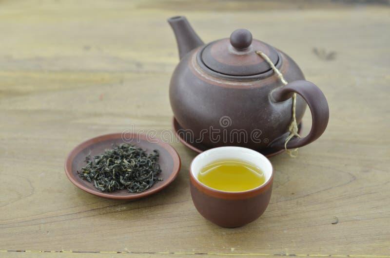 Tazza con tè, piatto con tè asciutto e teiera su fondo di legno fotografia stock