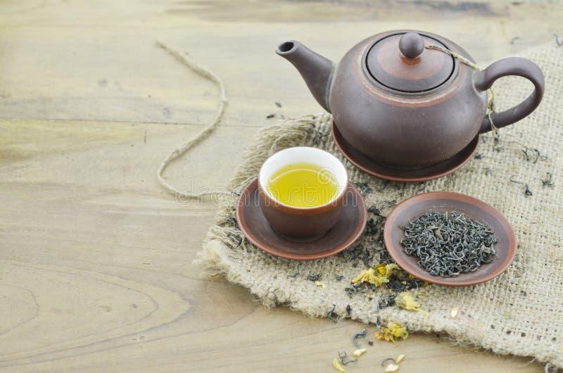 Tazza con tè, piatto con tè asciutto e teiera sulla tavola di legno fotografia stock