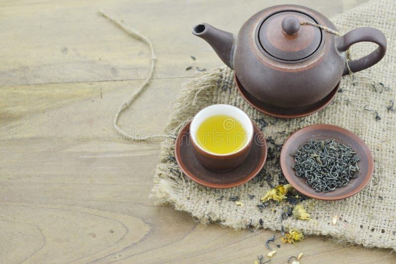 Tazza con tè, piatto con tè asciutto e teiera sulla tavola di legno immagini stock