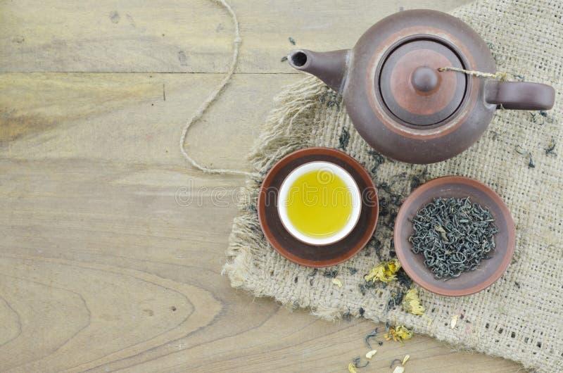 Tazza con tè, piatto con tè asciutto e teiera sulla tavola di legno immagine stock libera da diritti