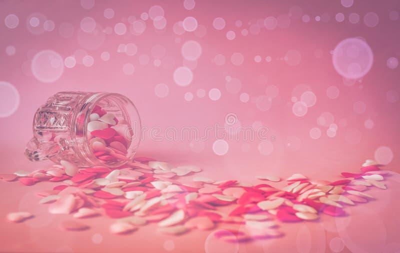 Tazza a cristallo con pochi cuori sul rosa fotografie stock