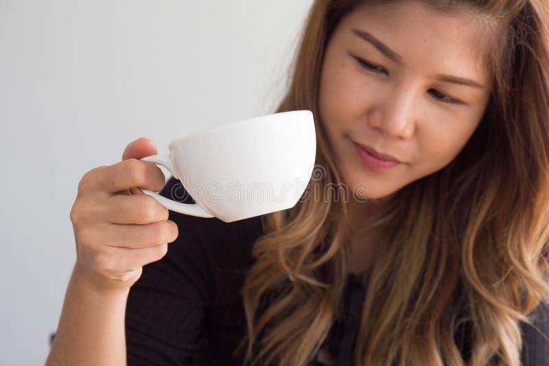 Tazza da caffè asiatica della tenuta e di sorveglianza della ragazza del primo piano in caffè immagine stock libera da diritti