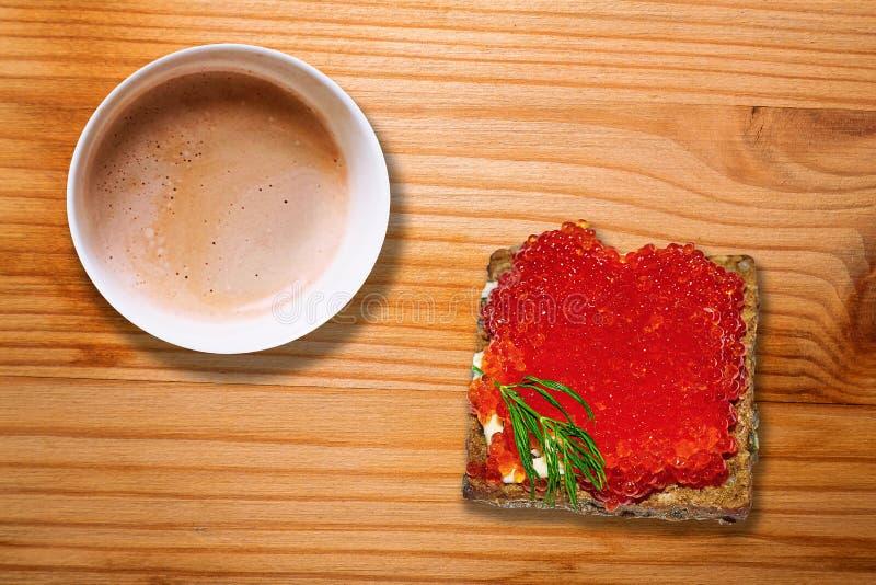 Tazza da caffè calda e panino rosso del caviale sullo scrittorio di legno immagine stock libera da diritti