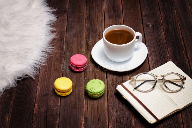 Tazza da caffè, maccheroni, blocco note e vetri Tavola di legno scura immagini stock